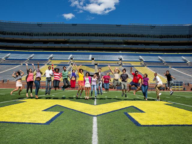 Students jumping in the air at the big house on the block M that is at midfield