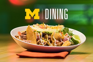 Graphic of the M|Dining logo placed above a white colored bowl of nachos with a lime wedge. The bowl is on a wooden table and placed on a red napkin.