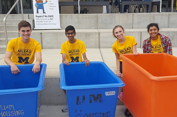 Four students smiling behind move-in bins
