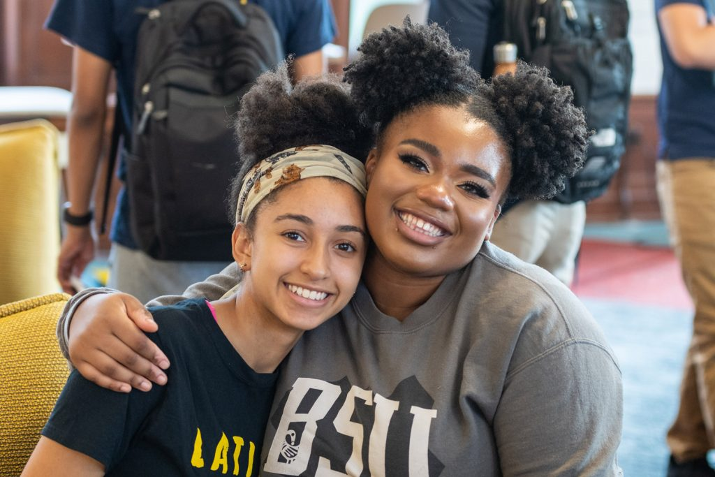 Two students smiling with arms around each other.